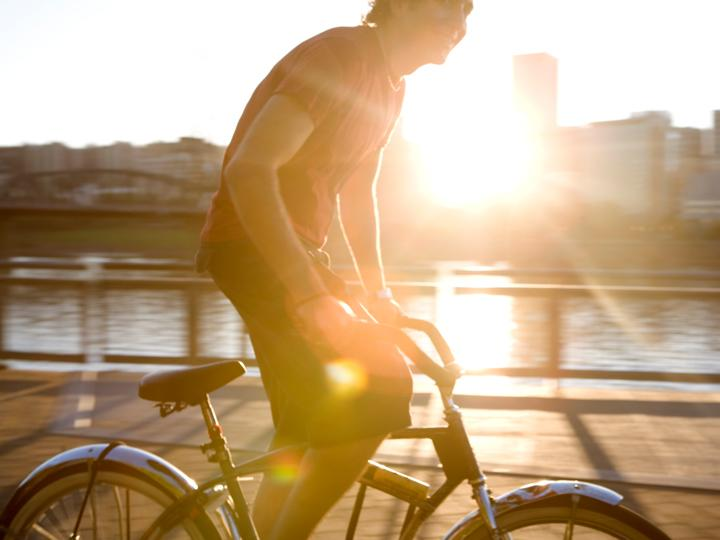 person riding bike silhouetted by the sun