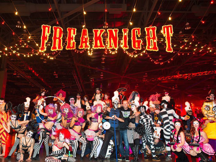 Freaknight sign with large group of people in costume posing underneath