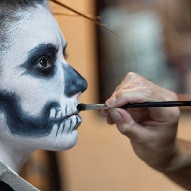 person getting their face painted as a skull
