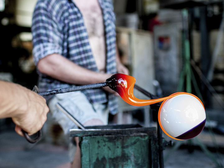a person shaping molten glass