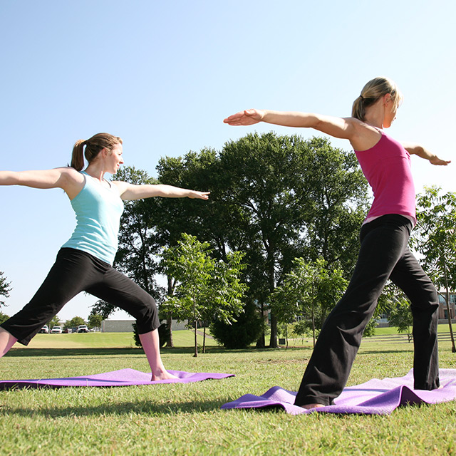 two women doing yoga in a park