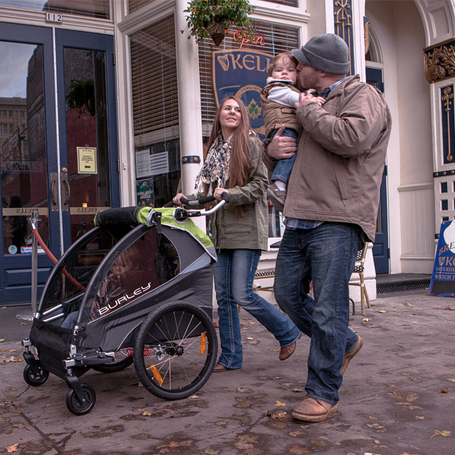 a couple walking down the street pushing a stroller and holding a toddler