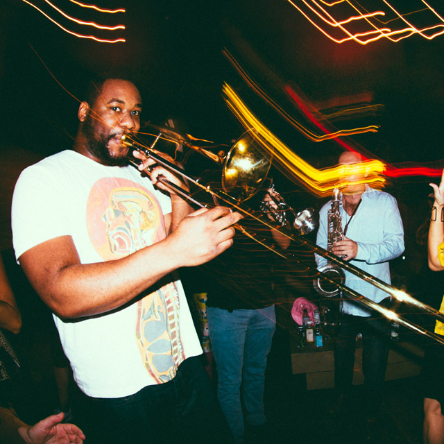 man playing a trombone in a club