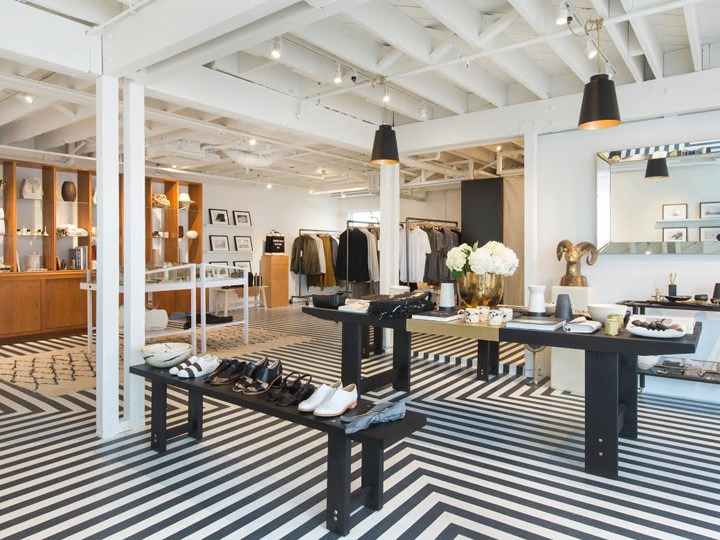 modern black and white interior with clothing racks and shoes spread sparsely around it