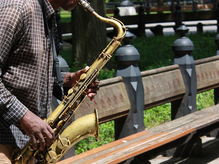 person playing a saxophone in a park