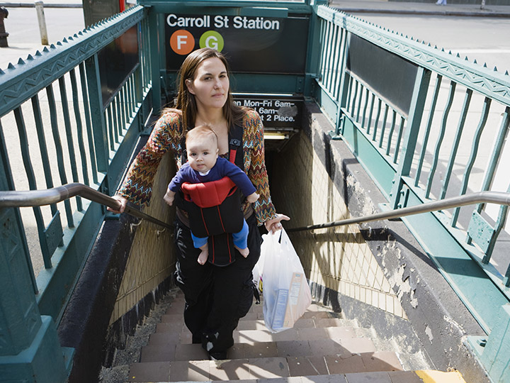 woman walking up subway stairs with baby in a front carrier