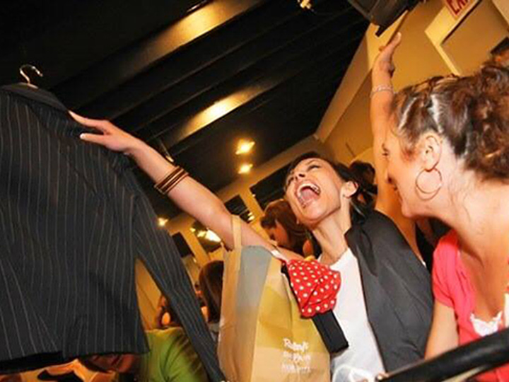 very excited woman holding a blazer in the air