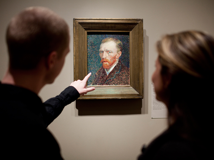 two people looking at a self portrait of Van Gogh