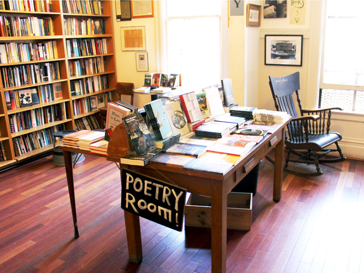 table in a bookstore with a sign that says Poetry Room