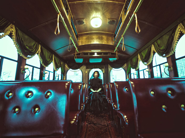 inside of an antique trolley with a creepy figure in the back