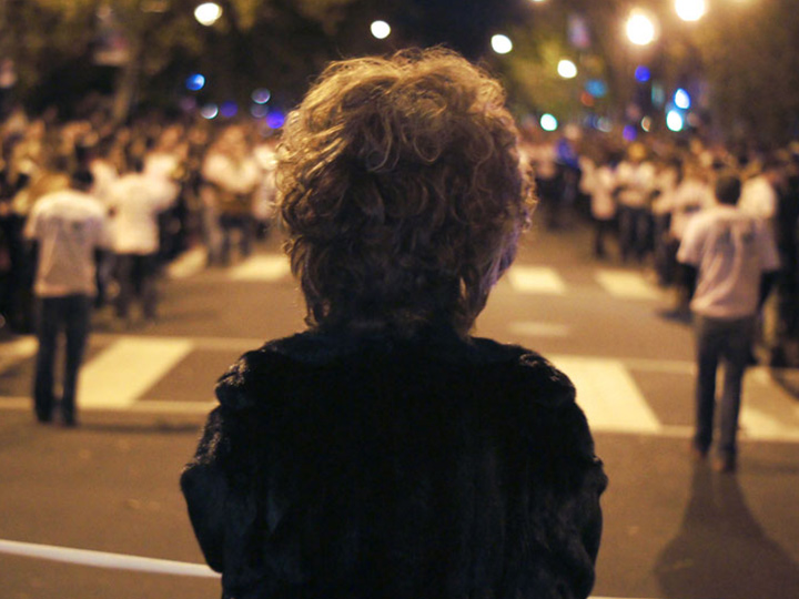 the back of a woman's head, with a crowd in the street in the background