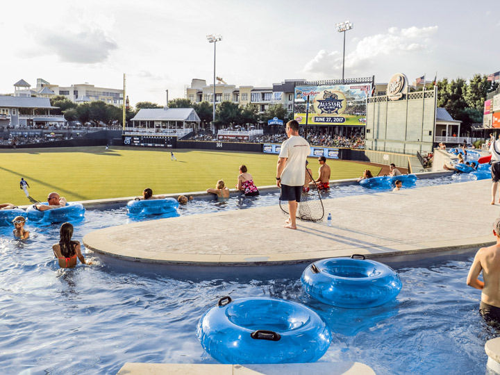 a pool with blue inflatables overlooking a baseball field