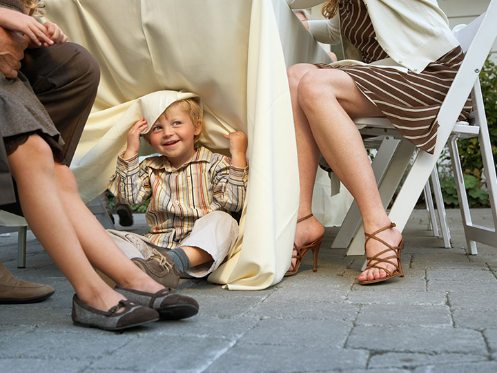 a child looking out from under a tablecloth