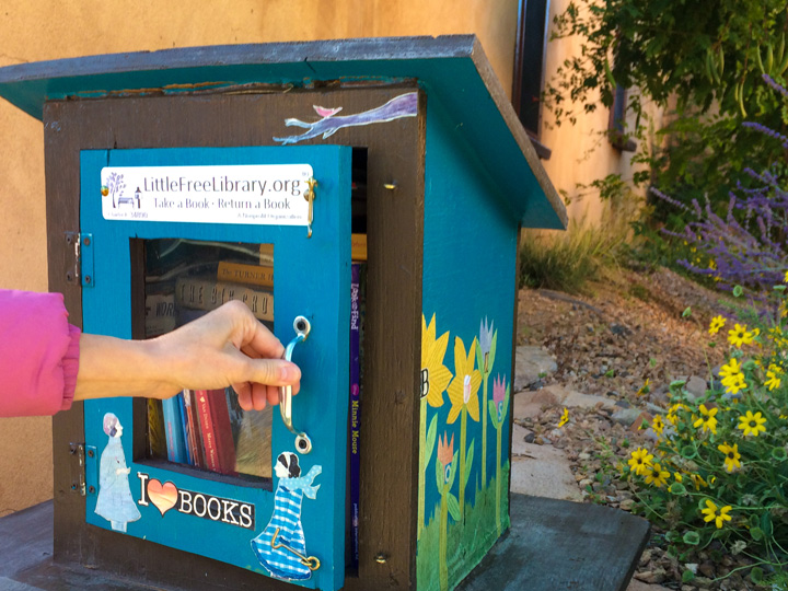 hand opening a little free library box