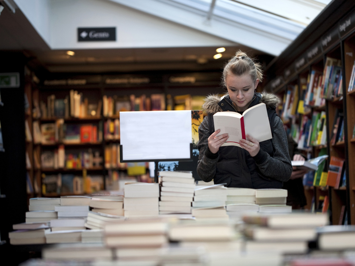 standing woman reading a book inside of a bookstore