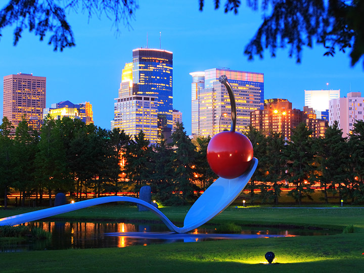sculpture of a large spoon with a cherry balanced on the end with a city behind