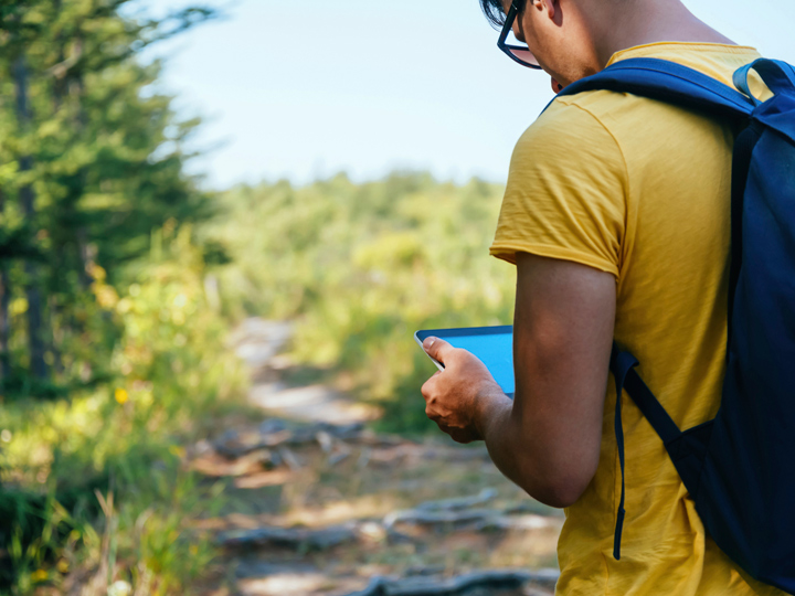 person on a hiking trail looking at a tablet