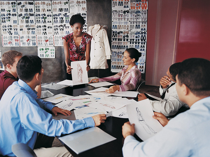 a woman displaying fashion drawings to people in a meeting room