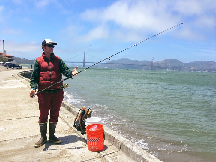man with a fishing pole on a shore with a suspension bridge in the background