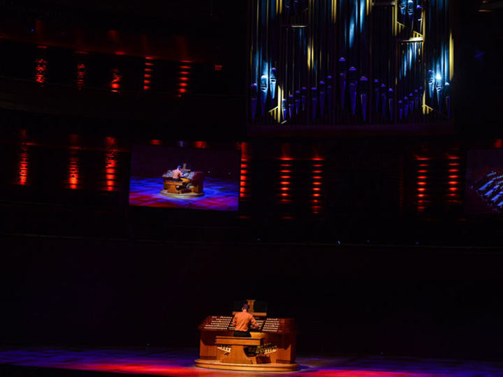 solitary person playing an organ on a dimly lit stage