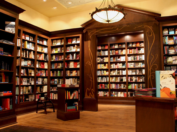 warmly lit book store interior with dark wood bookshelves