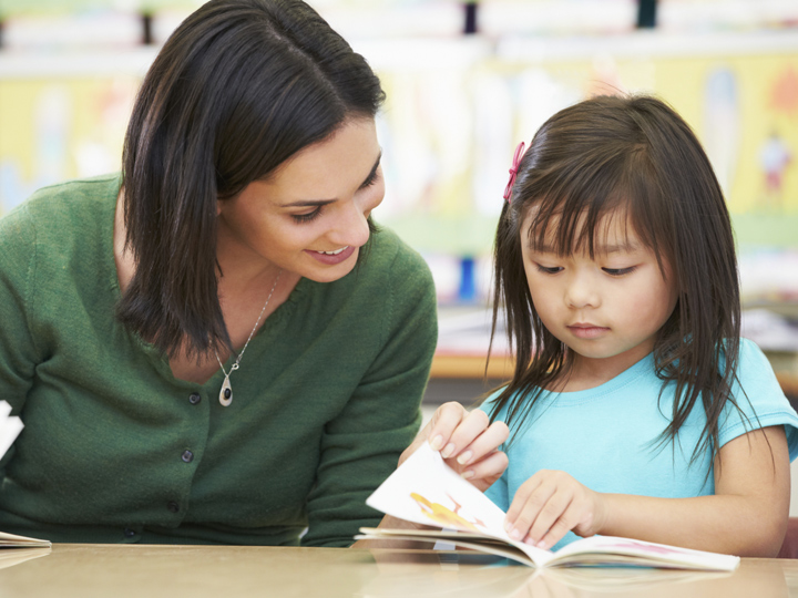 a smiling woman and child reading a book