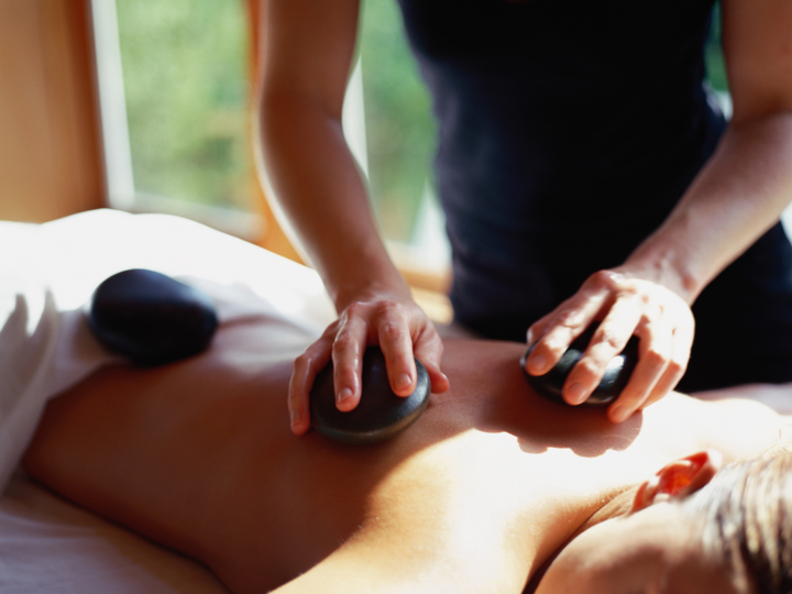 a woman getting a hot stone treatment