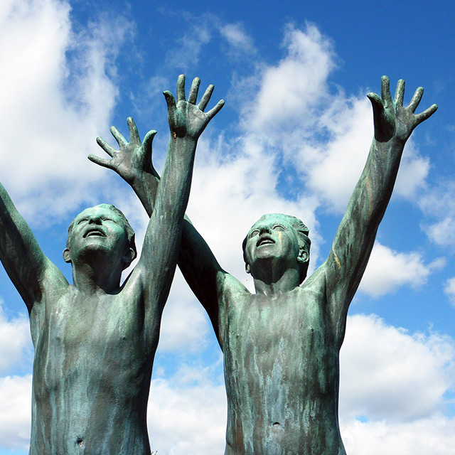 bronze metal statue of two men with their hands in the air