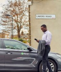 man in a suit booking a zipcar on his phone