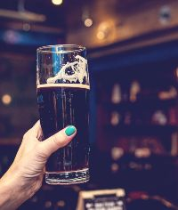 woman holding up a pint of craft beer