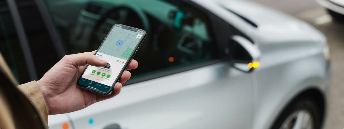 Person tapping on cell phone in front of a Zipcar
