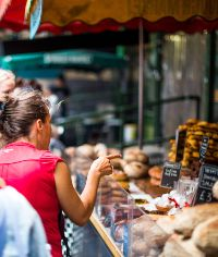 woman pointing at baked goods in a market