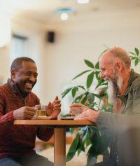 2 men talking around a table