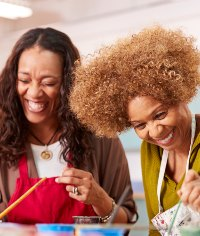 2 ladies laughing whilst doing pottery painting