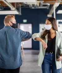 2 people elbow bumping whilst wearing masks in the office