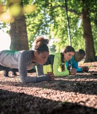 3 people doing a plank at a group outdoor exercise