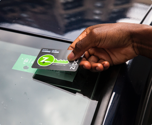A hand holding a Zipcard to a windshield sensor