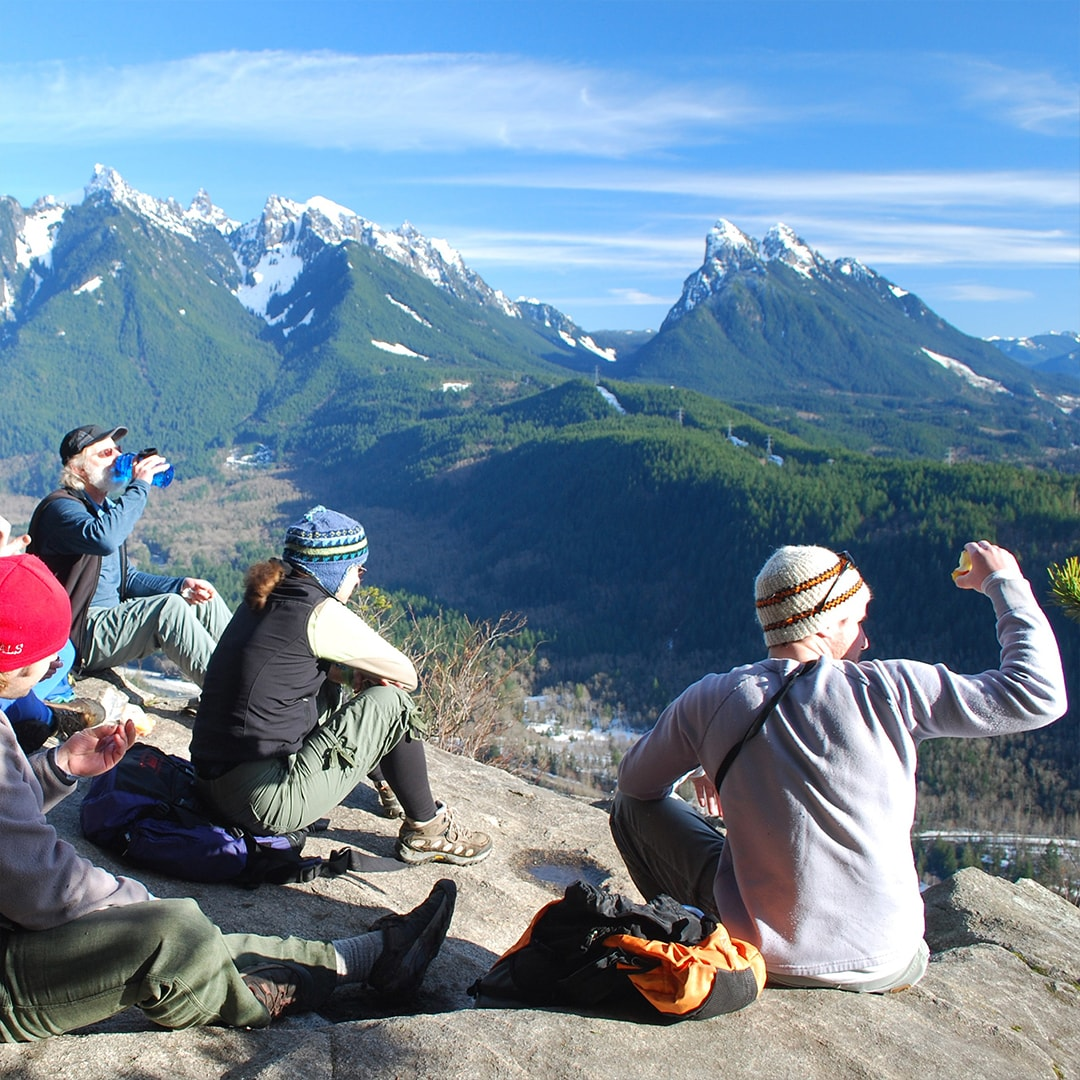 people sitting on the ground with mountains in the background