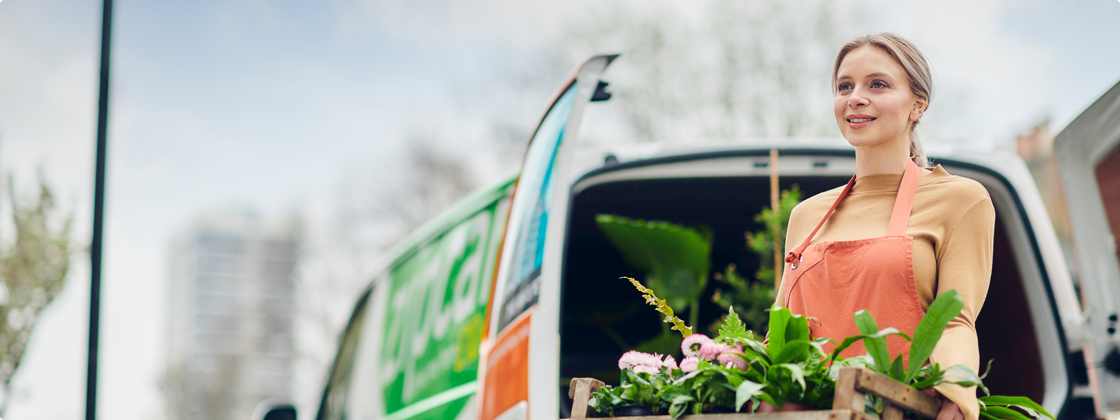 woman standing next to a Zipvan holding plants