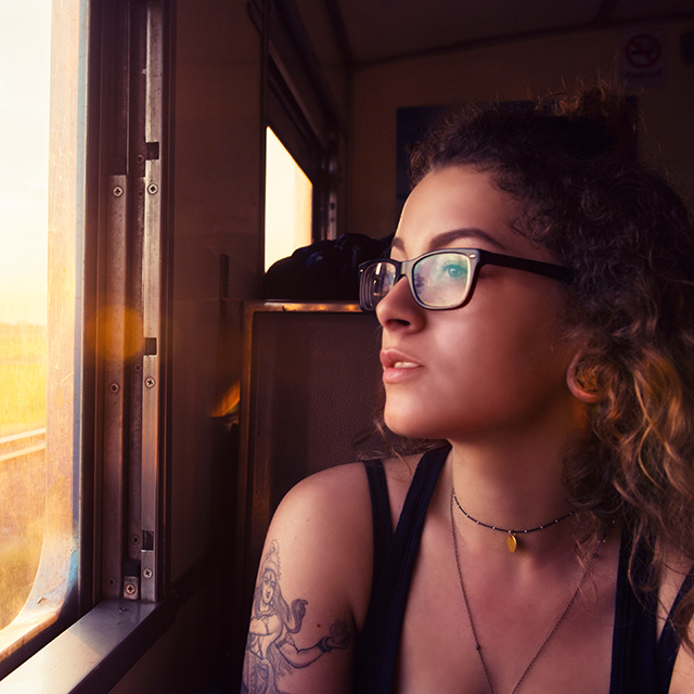 woman looking out a train window