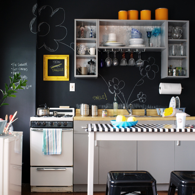 a modern kitchen with black walls and white cabinets