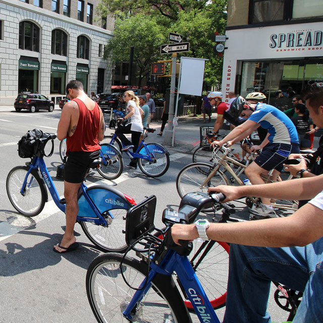 group of bicyclists stopped on a city street