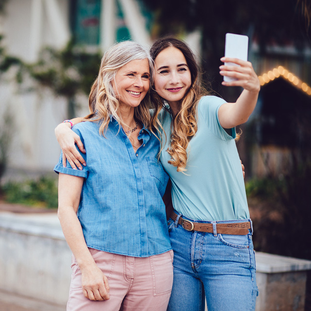young woman hugging older woman while taking a selfie