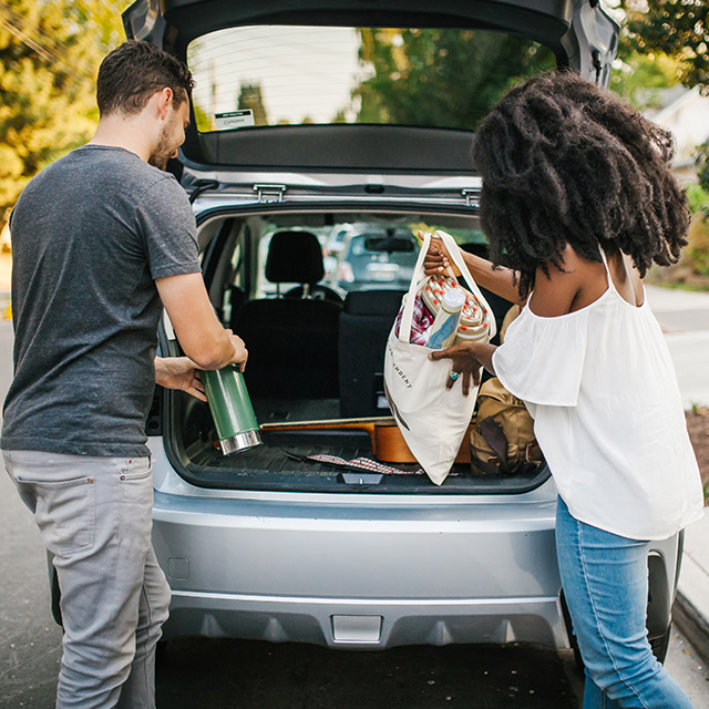 Two people load things into the trunk of a Zipcar.