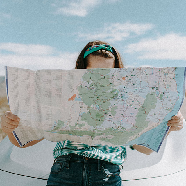 woman looks at a map outside of her Zipcar