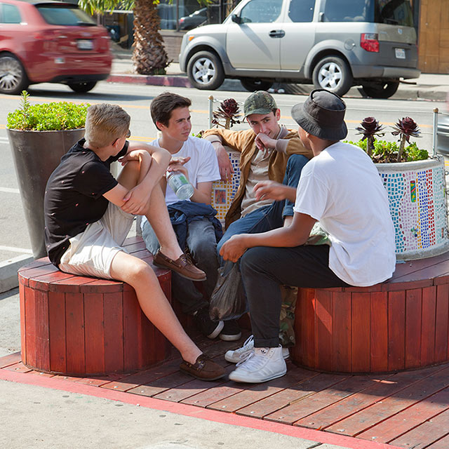 group of men sitting on benches and chatting on a street