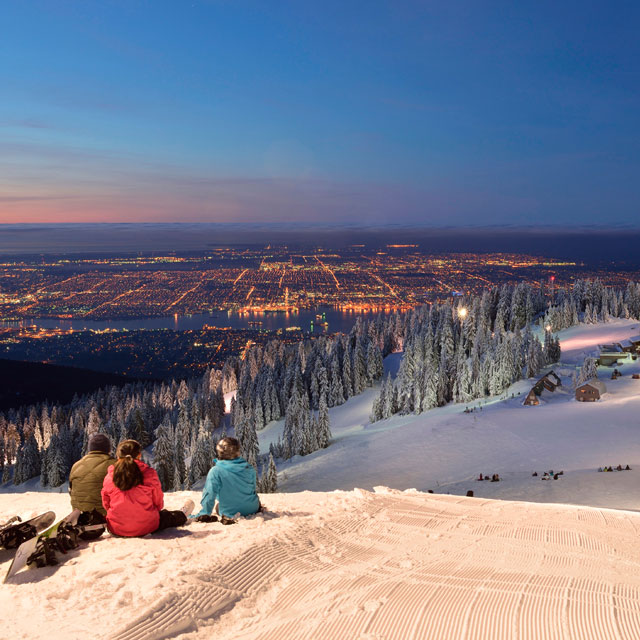 group of people sitting on a ski slope at night