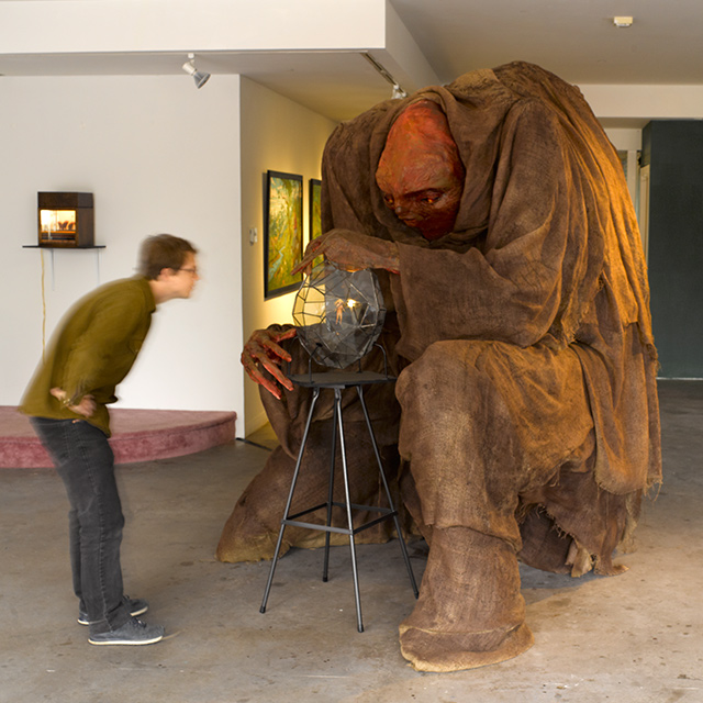 person looking at a giant figure that is sitting down