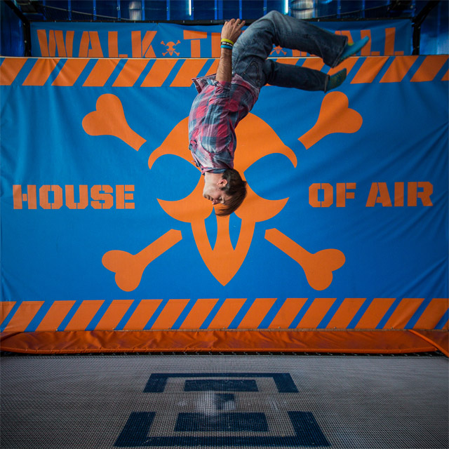 photo of a man upside down above a trampoline with a House of Air sign behind him