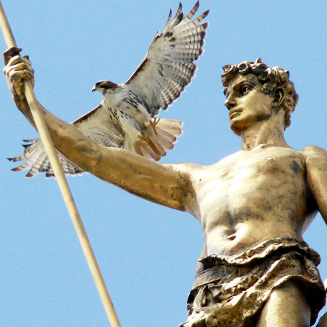 Marble statue of a man holding a spear and a falcon on his upper arm